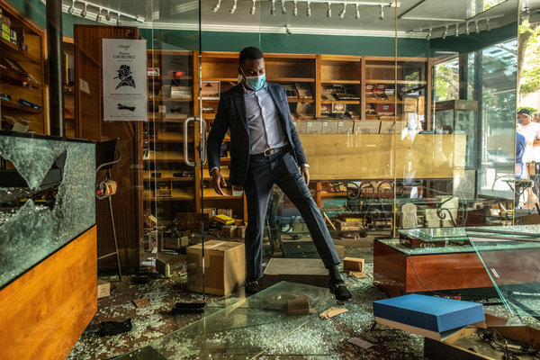 An employee at the Lone Wolf Cigar Company in Santa Monica, Calif., surveyed the damage done to the store by looters on Sunday.