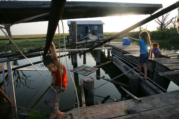 Children played near their homeon Isle de Jean Charles, La., a few months after Hurricane Katrina struck in 2005.