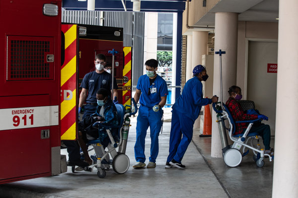Health care workers help patients outside the Houston Medical Center on Thursday. Houston's mayor has said that I.C.U.s there were nearly at capacity.