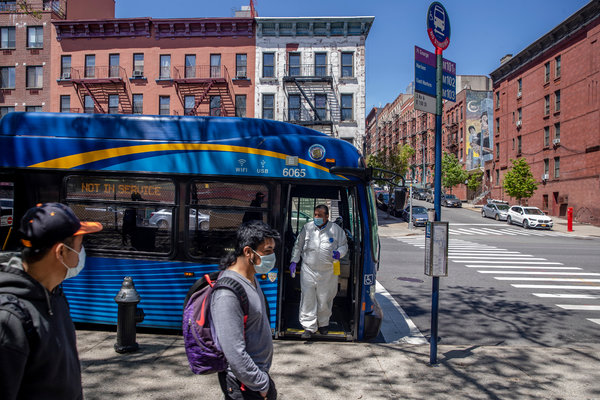 Raymond Sanchez, an M.T.A. driver, disinfecting buses during the changing of shifts in East Harlem in New York in May.