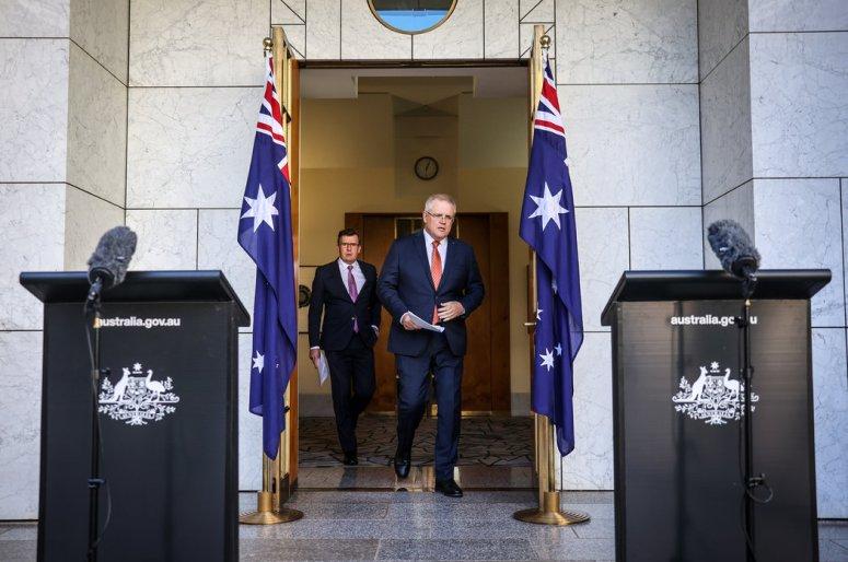 周四,澳大利亚堪培拉,澳大利亚总理斯科特·莫里森(右)和代理移民部长艾伦·塔奇到达发表声明的现场。