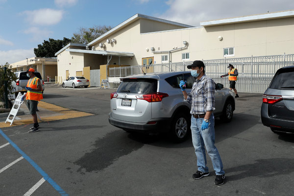 Families in cars are directed as they line up to receive computers for San Diego Unified School District distance learning, in April in San Diego.
