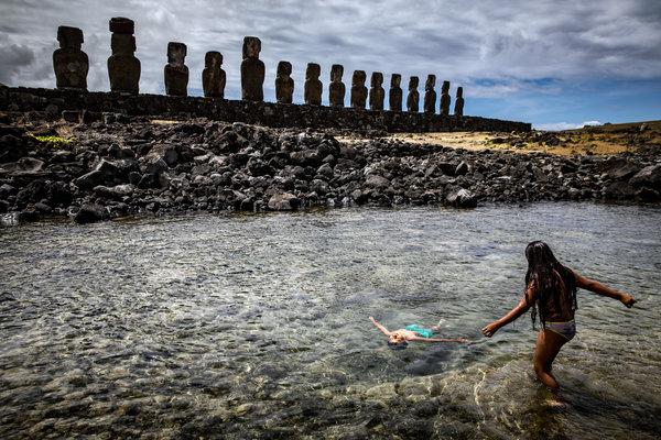 Children play in the ocean behind Ahu Tongariki on Easter Island.
