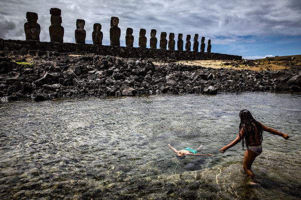 Children play in the ocean behind Ahu Tongariki on Easter Island.