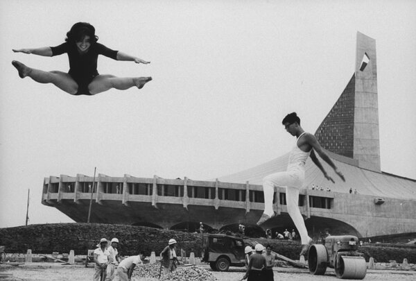 Gymnasts, in 1964, outside the newly-built Yoyogi National Gymnasium, designed by Kenzo Tange and constructed to house the aquatics and basketball competitions. This year handballers were to have faced off beneath its plunging canopies of steel.