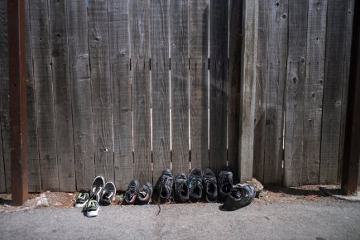 Shoes sitting outside Karla Lorenzo's home to disinfect. She confined herself to the closet for days to avoid spreading the virus to her children.