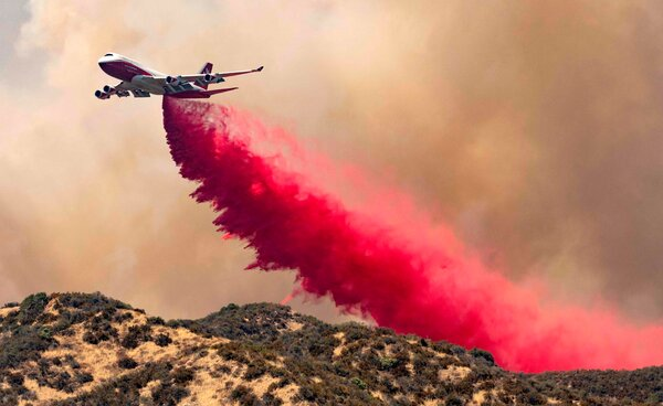 A 747 Supertanker dropped fire retardant along a ridge ahead of the Apple Fire on Saturday.