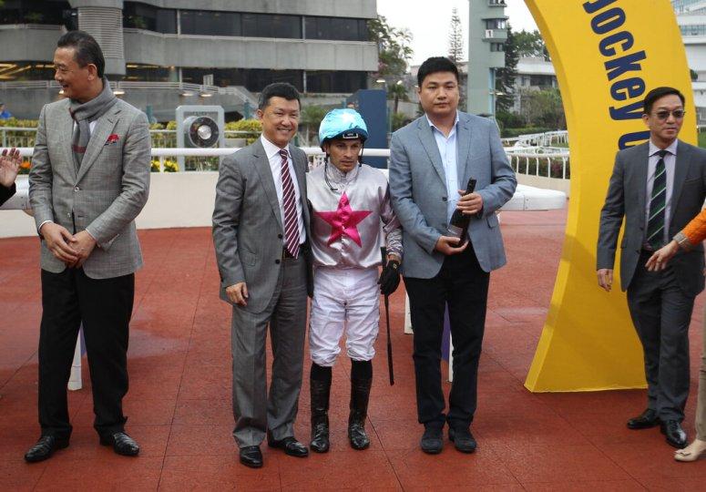 """手中拿着一个葡萄酒瓶的蔡华波。他是栗潜心的伴侣,拥有一匹名为""""赤兔宝驹""""的赛马。图为他在2017年香港沙田马场的一场比赛上庆祝赛马获胜。"""