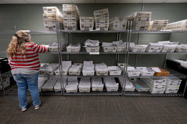 An election worker processes mail-in ballot requests at the Johnson County election office in Olathe, Kan.