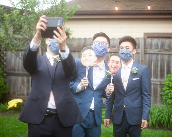 Mr. Moon and his attendants pose for photos with face cards of those in the wedding party who were unable to attend.