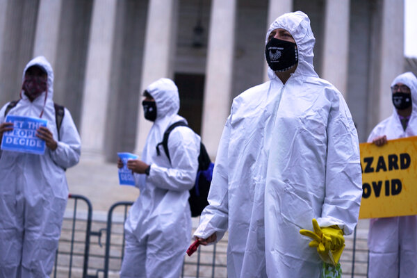 Protesters dressed in personal protective equipment outside the Supreme Court on Monday.
