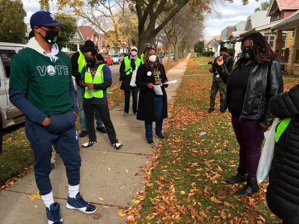 George Hill of the Milwaukee Bucks, left, helped get out the vote in Milwaukee on Saturday.