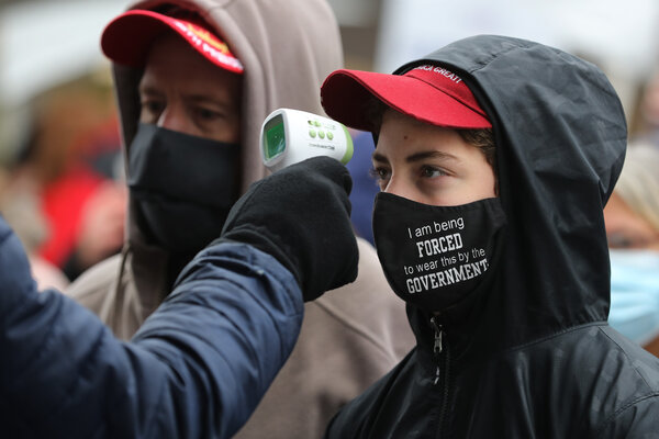 Supporters of President Trump have their temperature taken as a precaution against the coronavirus before attending a campaign rally at Capital Region International Airport in Lansing, Mich., on Tuesday.