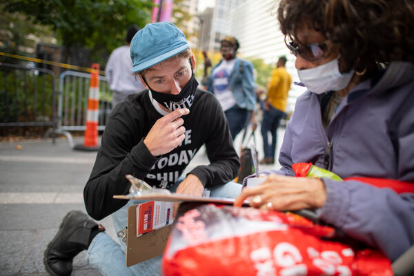 A volunteer helps a woman complete an early ballot form outside of Philadelphia City Hall at the satellite polling station in Philadelphia, Pennsylvania.