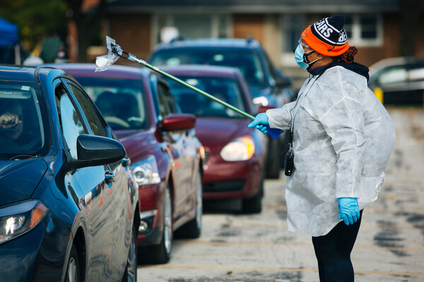 An essential worker uses a tool to take a self-administered Covid-19 test from a car at a testing site in Chicago.