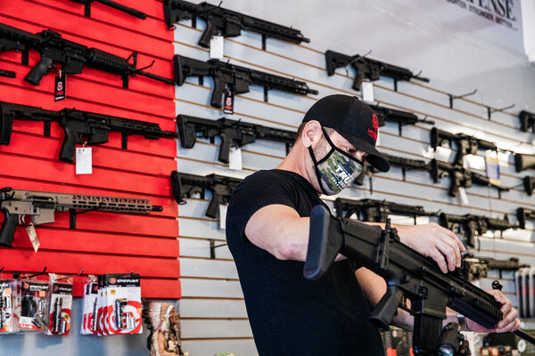 Brandon Wexler, the owner of Wex Gunworks in Delray Beach, Fla., showing a gun to potential customers.