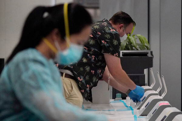 Dignity GoHealth workers runAbbott ID Now rapid tests for United Airlines passengers in San Francisco. United is hoping expanded testing can help reopen international travel.