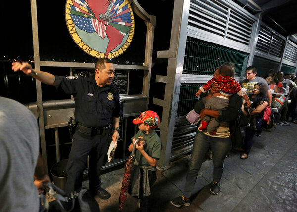 A U.S. Customs and Border officer guiding asylum-seeking migrants across a bridge from Nuevo Laredo, Mexico, into the U.S.