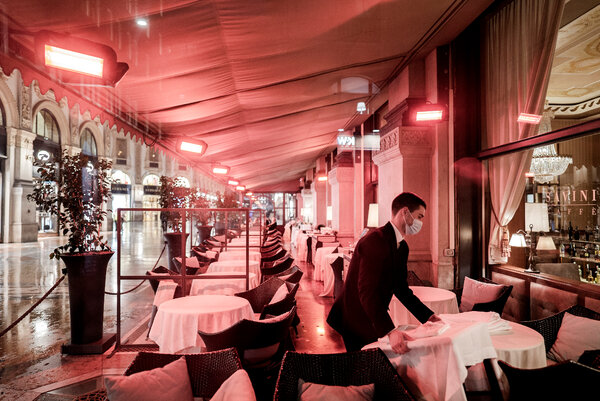 Collecting tables at a restaurant in Milan. All restaurants, clubs and bars must close at 6 p.m. as part of a government decree.