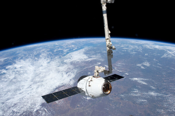 The SpaceX Dragon commercial cargo spacecraft arriving at the space station via Canadarm2 in 2012.