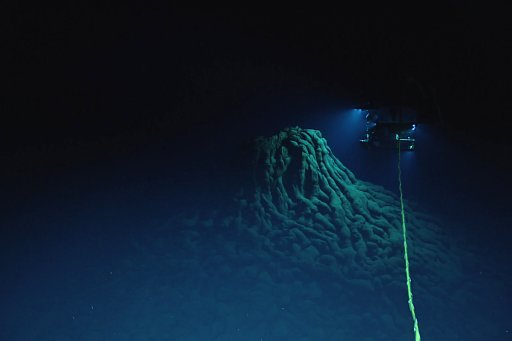 An ROV examines a vent on top of a mound of pillow lava near a hydrothermal vent at the bottom of the deep sea