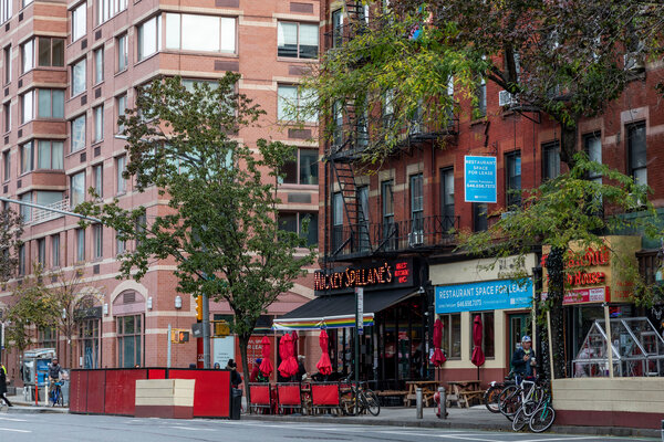 Restaurants and stores line Ninth Avenue in buildings that also contain apartments.