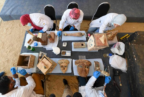 Archaeologists cleaned statues and funeral masks on Saturday as the trove was introduced to journalists.