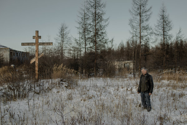 Mikhail Shibisty, 63, a shop owner who runs an exhibit on Soviet forced-labor camps, on the site of a prisoner graveyard. He erected a Russian Orthodox cross in honor of those who died.
