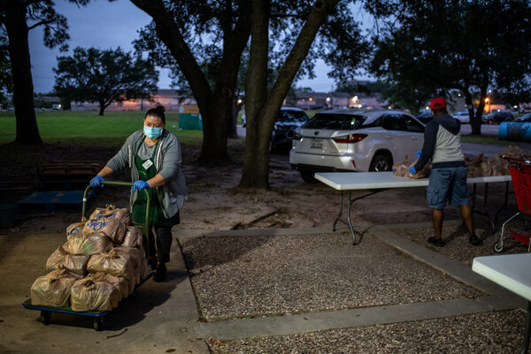 Maria Lomeli, a volunteer at a food bank in Houston, preparing to distribute food before sunrise in October.