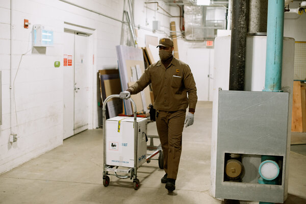 Dallas White, a UPS driver, wheeled a shipment of Covid-19 vaccine into UPMC Children's Hospital of Pittsburgh on Monday.