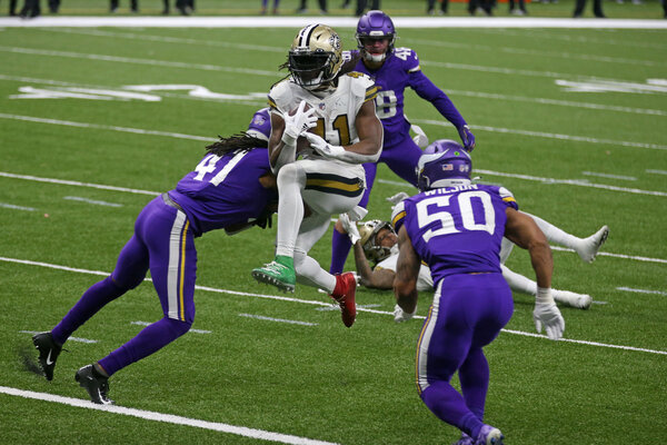 Alvin Kamara (41) jumping into the end zone between the Minnesota Vikings' Anthony Harris (41) and Eric Wilson (50) during last weekend's game.