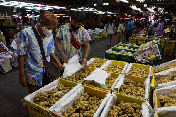 Shoppers peruse the longan fruit for sale at the Talaad Thai Wholesale Market in Bangkok, Thailand.