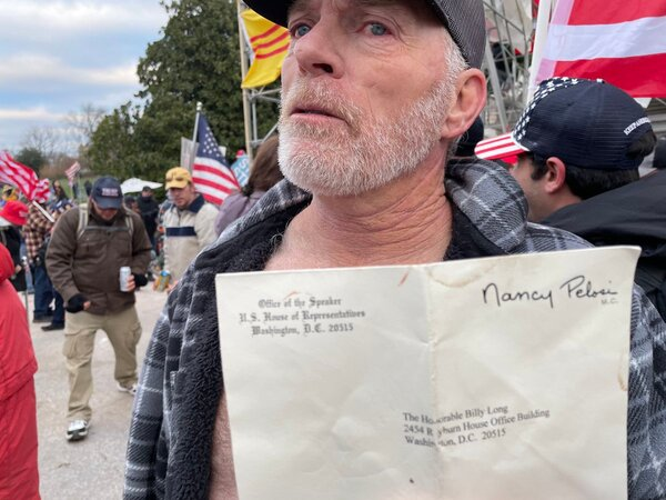 Richard Barnett, 60, from Gravette, Ark., showed off the envelope he took from Ms. Pelosi's office on Wednesday.
