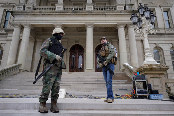 Armed men outside of the State Capitol in Lansing, Mich., on Wednesday.