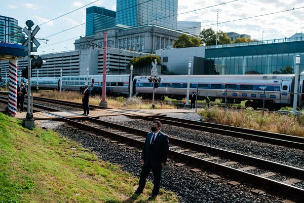 Secret Service agents stood in front of an Amtrak train that Joseph R. Biden Jr. was set to ride while campaigning in September. Mr. Biden, now the president-elect, will no longer take Amtrak to his inauguration.