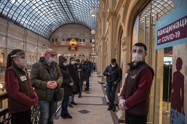 People wait in line to receive the Sputnik V coronavirus vaccine at the State Department Store GUM in Moscow.