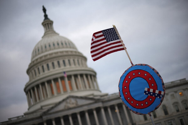 A supporter of President Donald Trump flies an American flag with a QAnon symbol outside the Capitol on Jan. 6.