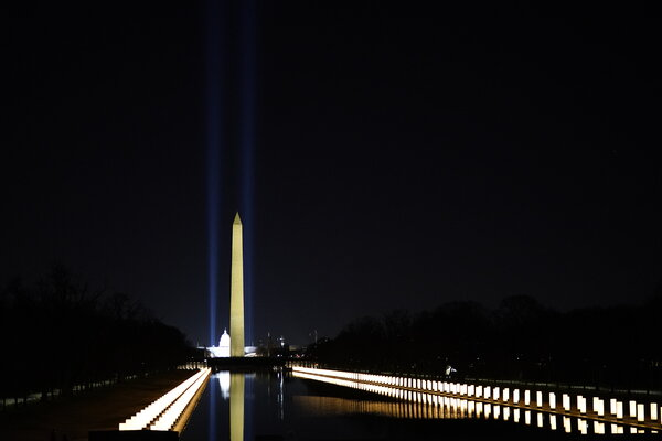 Lights honoring those who have died in the pandemic surround the Reflecting Pool on the National Mall, a somber setting for the celebratory concert.