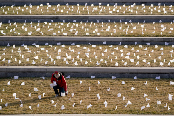 A man placing flags at the National World War I Museum and Memorial in Kansas City on Tuesday. The flags represent the area residents who died of coronavirus.
