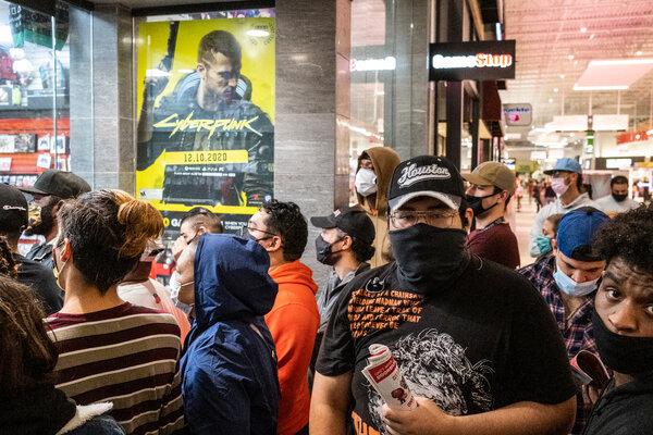 Shoppers wait outside of a GameStop on Black Friday.An online community of traders seem to be fueling a spike in the store's share price.