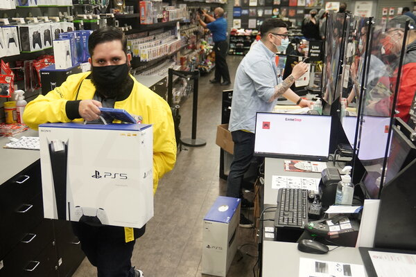 An employee at a GameStop store in Manhattan in November with a Sony PS5 console. The new machines led to big profits in software and network fees for Sony.