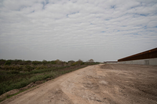Land cleared for the construction of the border wall as an enforcement zone is seen to the south of the wall near Alamo.