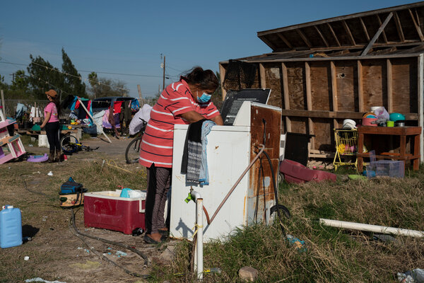 Erika Aguilar, 40, a mother of three, takes out clothes from the washer at her home in Edinburg, Texas. Her kitchen, as seen behind her, rolled over during Hurricane Hanna last summer.