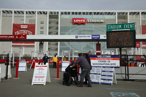 People arrive at Levi's Stadium, a mass vaccination site in Santa Clara, Calif.