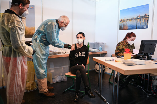 A health care worker received her first dose of the AstraZeneca Covid-19 vaccine at a vaccination center in Rostock, Germany, on Friday.