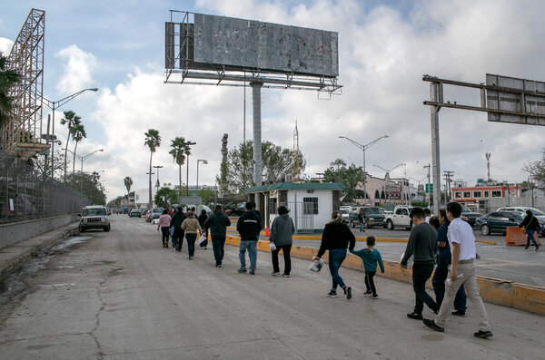 Asylum seekers walk back into Mexico after an immigration court hearing in December 2019.