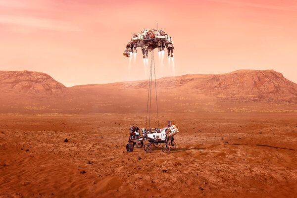 An artist's concept of the Perseverance rover, bottom, being dropped on the Martian surface by the descent stage.