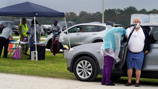 A man gets the coronavirus vaccine at an outdoor vaccination site on Wednesday in Bradenton, Fla.