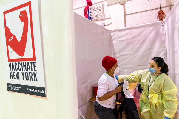 Rita Alba, right, a registered nurse, directs Alba Carrasco to the recovery area after giving her the first dose of the coronavirus vaccine at a pop-up vaccination site at the Bronx River Addition NYCHA complex in January.