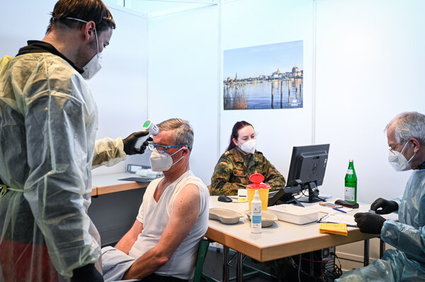 An emergency paramedic takes the temperature of Uwe Einecke, 59, before he is vaccinated in Rostock, Germany.